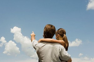 Father and daughter looking at clouds